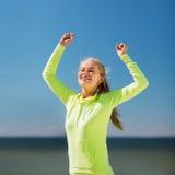 庆祝胜利的妇女赛跑者 免版税库存图片