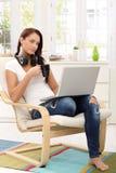 享受与膝上型计算机的俏丽的女孩业余时间 免版税库存图片
