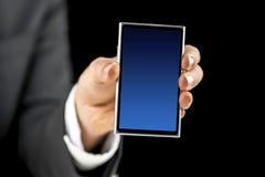 拿着有蓝色空的屏幕的商人手机 库存图片