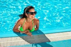 有精密乳房的逗人喜爱的愉快的比基尼泳装妇女在游泳池 免版税库存照片