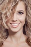 美丽的微笑的妇女。健康长的卷发 免版税库存照片