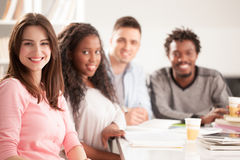 一起坐微笑的大学生 库存照片