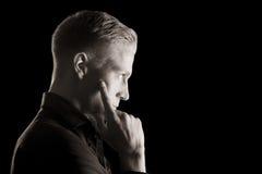 Низкий ключевой портрет профиля молодого человека, черно-белый. Стоковые Изображения RF