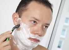刮他的胡子的一个年轻人的画象 库存图片