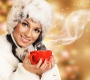 有一个红色杯子的年轻和美丽的妇女在圣诞节背景 免版税库存图片
