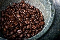 在花岗岩研磨机的烤咖啡豆 图库摄影