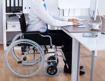 坐轮椅和使用计算机的商人 库存照片