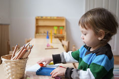 男孩在有图画蜡笔的幼儿园 图库摄影