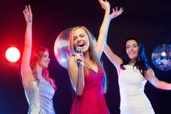Τρεις χαμογελώντας γυναίκες που χορεύουν και που τραγουδούν το καραόκε Στοκ Φωτογραφία