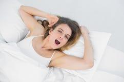 说谎在她的床上的年轻打呵欠的妇女在卧室 免版税库存图片