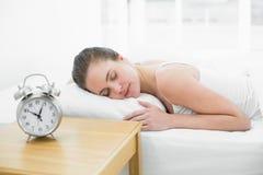 睡觉在与焦点的床上的妇女在闹钟 免版税图库摄影