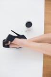 Коммерсантка в высоких пятках ослабляя ноги вверх в столе офиса Стоковая Фотография RF