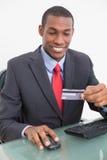 Усмехаясь молодой бизнесмен Афро делая онлайн покупки Стоковая Фотография