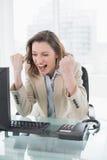 欢呼与握紧拳头的女实业家在办公桌 免版税库存图片
