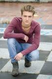 可爱的蓝眼睛,白肤金发的年轻人坐方格的地板 免版税库存图片