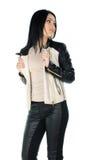 摆在和显示她的皮革外套的美丽的浅黑肤色的男人 免版税库存照片