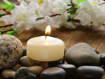 静物画每被点燃的蜡烛和石头 库存图片
