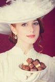 美丽的红头发人妇女用糖果。 免版税库存图片