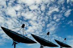 Τρία δορυφορικά στοιχεία μετάδοσης πιάτων όσον αφορά το μπλε ουρανό υποβάθρου Στοκ Φωτογραφία