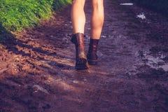走沿泥泞的足迹的少妇 免版税库存图片