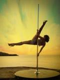 妇女锻炼反对日落海风景的杆舞蹈。 免版税库存图片