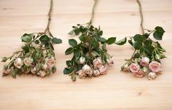 Τρία τριαντάφυλλα ψεκασμού στο ξύλινο υπόβαθρο Στοκ Φωτογραφίες