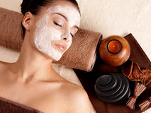 放松与在面孔的面部面具的妇女在美容院 库存照片