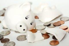 溢出的硬币包围的残破的小存钱罐 免版税图库摄影