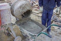 从水泥搅拌车的建造者工作者倾吐的水泥到独轮车里 免版税库存图片