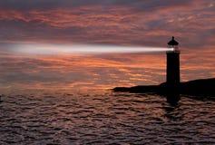灯塔探照灯射线通过海洋空气在晚上。 库存照片