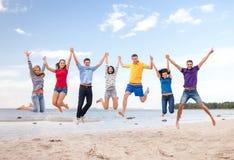 跳跃在海滩的小组朋友 免版税库存图片