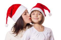 亲吻面颊的愉快的母亲女儿在圣诞节帽子 库存图片