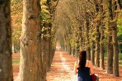 有步行沿着向下它的妇女的长的树木繁茂的道路 免版税库存照片