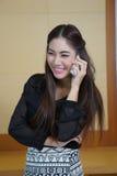 年轻女商人讲手机与甜微笑。 图库摄影