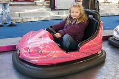 驾驶一辆碰撞用汽车的女孩 免版税库存图片