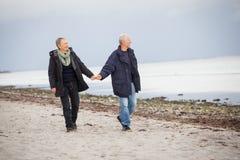 成熟走在海滩的愉快的夫妇在秋天 免版税库存照片