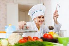 无边女帽的愉快的厨师在厨房工作 库存照片