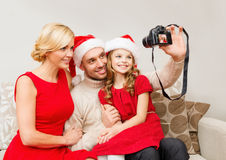 在圣诞老人拍照片的帮手帽子的微笑的家庭 免版税库存照片