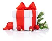 白色礼物盒被栓的红色缎丝带弓,三圣诞节球 免版税库存照片