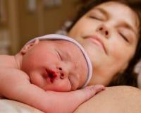 休息在交付以后的母亲和婴儿孩子 免版税库存照片
