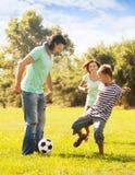 有使用与球的十几岁的儿子的愉快的父母 免版税库存图片