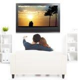 在看与遥控的沙发的夫妇电视 库存图片