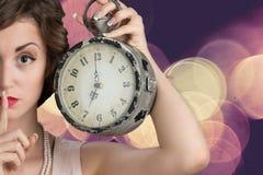 拿着大时钟的少妇 图库摄影