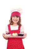 小女孩厨师有蛋糕的举行板材 免版税库存图片
