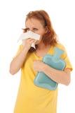 红发与热的水瓶的妇女吹的鼻子 库存图片