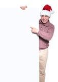 老偶然圣诞老人人指向一个大空白的广告牌 免版税库存照片