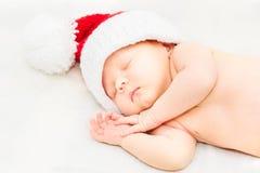 可爱的睡觉的新出生的婴孩在圣诞老人帽子,圣诞节 免版税库存图片