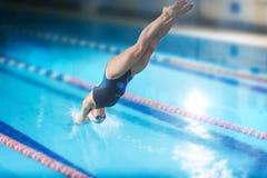女性游泳者,跳进室内游泳池的那。 免版税库存图片