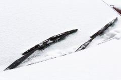 用雪盖的汽车挡风玻璃 免版税库存照片