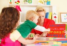 幼儿园孩子在有老师的教室 免版税库存照片